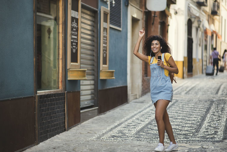 beautiful mixed girl listening to the music happy in the street Architecture Beautiful Woman Beauty Building Exterior Built Structure Casual Clothing City Fashion Front View Full Length Hairstyle Holding Leisure Activity Lifestyles One Person Outdoors Real People Standing Women Young Adult Young Women