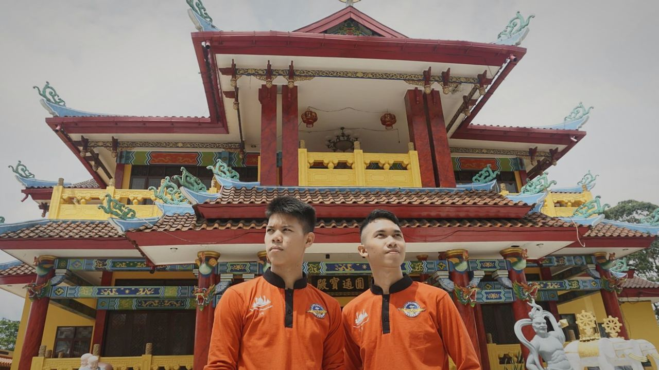 LOW ANGLE VIEW OF MEN STANDING OUTSIDE TEMPLE