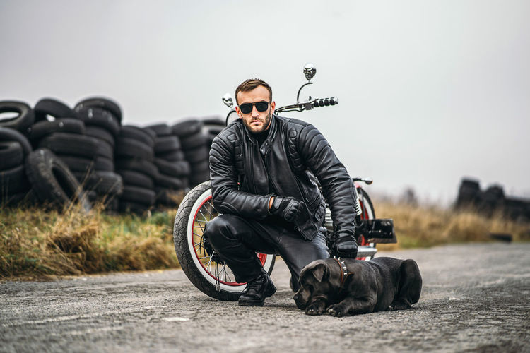 Young man sitting with bicycle on road