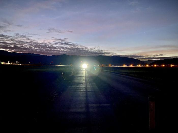 Illuminated road against sky at sunset