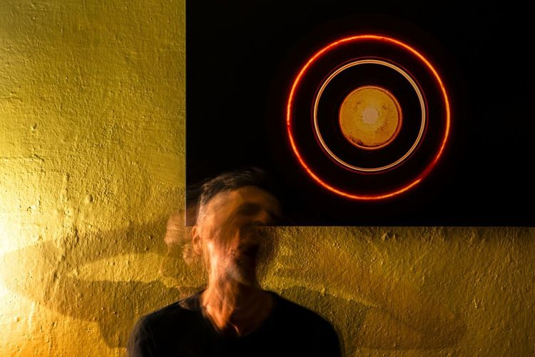 Blurred motion of man standing against illuminated wall
