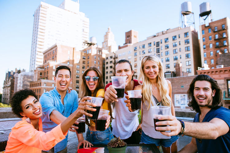 Portrait of people holding drinks against building
