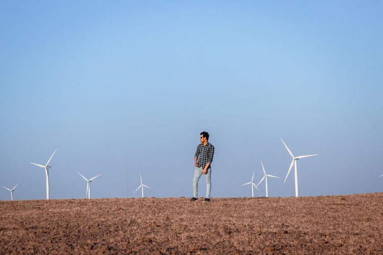 Full length of man standing on landscape with wind turbines against clear blue sky