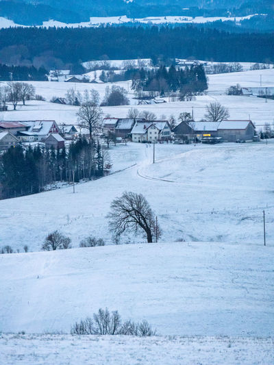 Snow covered field by buildings in city