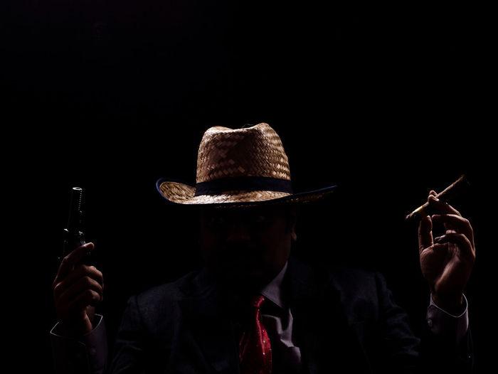 Man holding cigar and handgun against black background
