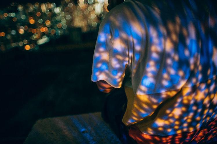Lights reflecting on man sitting on retaining wall at night