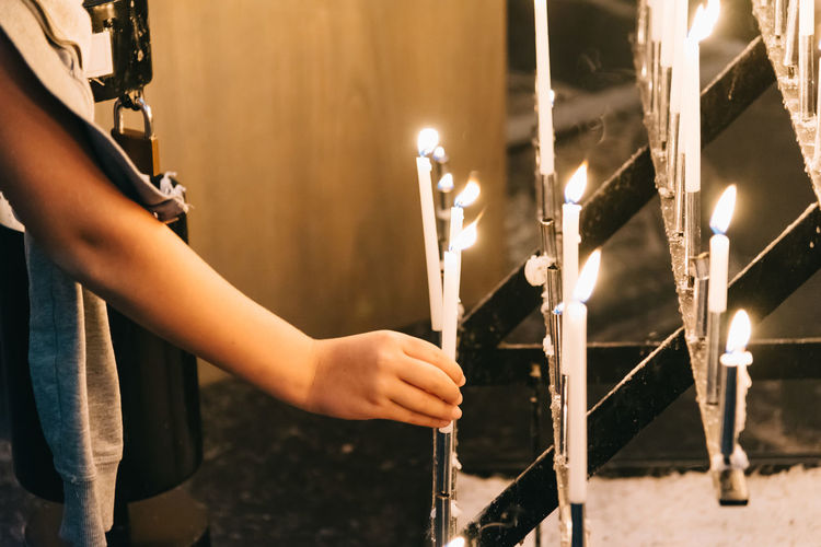 Young woman praying in church with candles Candle Candlelight Candles Cathedral Christ Christian Church Day Faith God Holding Hope Human Body Part Human Hand Indoor Indoors  Lifestyles One Person Pray Praying Real People Religion Worship Young Young Adult