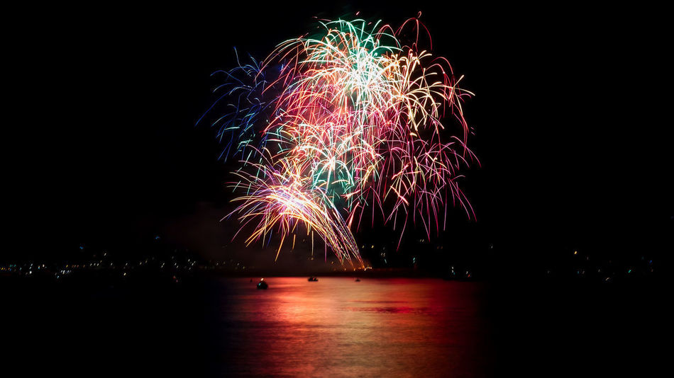 Arts Culture And Entertainment Celebration Dark Event Exploding Firework Firework - Man Made Object Firework Display Glowing Illuminated Light Long Exposure Motion Multi Colored Nature Night No People Reflection Sky Sparks Water Waterfront