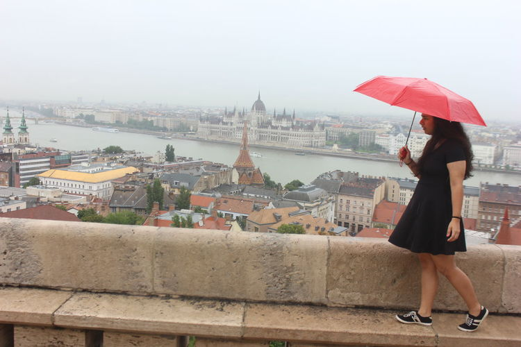 Full length of woman holding umbrella with hungarian parliament building in background