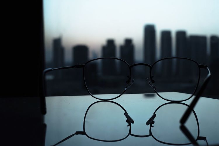 Close-up of eyeglasses against buildings in city
