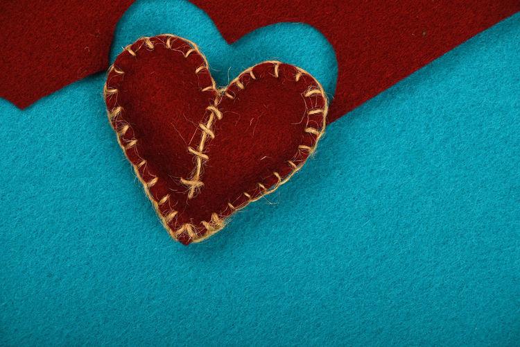 Close-up of felt craft heart over blue background