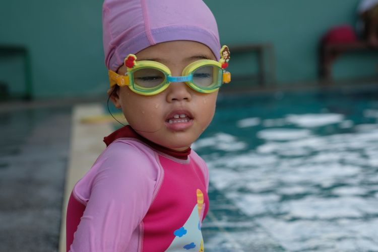 Cute girl wearing swimming goggles by pool