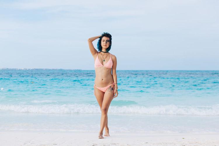 Full length of woman in bikini standing at beach against sky
