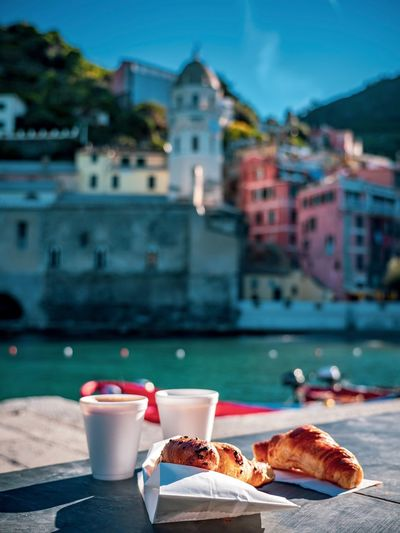 Croissant with coffee on table against buildings in city
