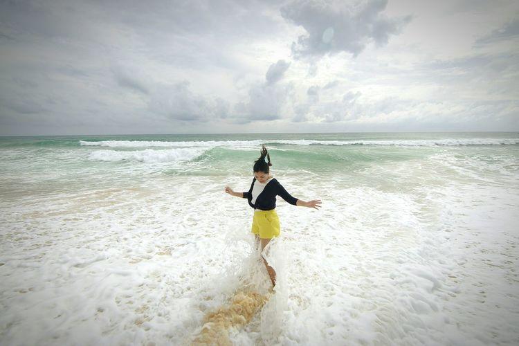 Playful woman enjoying on sea shore against cloudy sky