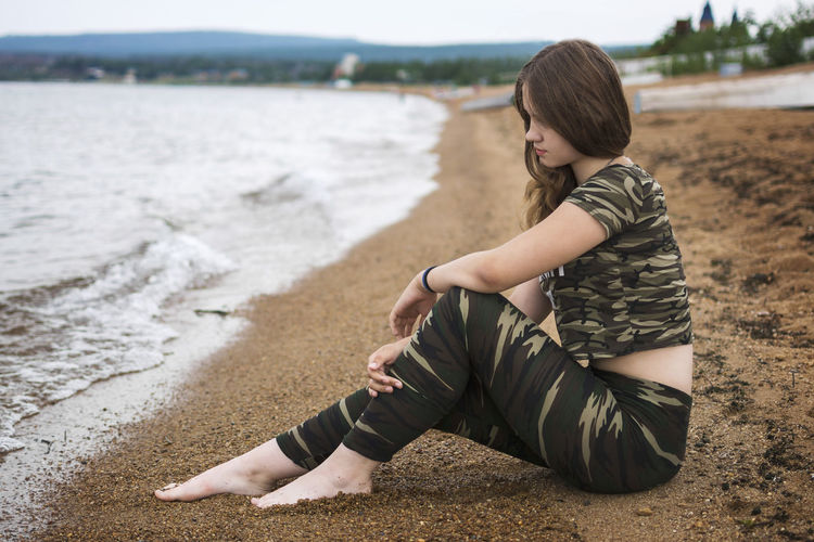 Side View Of Woman Sitting On Beach