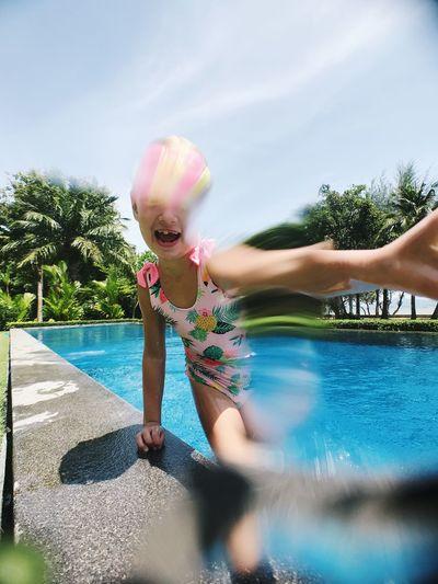 Girl in swimming pool against sky