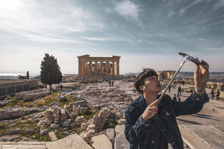 Acropolis Athens Greece Athens, Greece Acropolis Architecture Sky One Person Lifestyles Built Structure Real People History Leisure Activity The Past Ancient Old Ruin Young Adult Building Exterior Nature Cloud - Sky Day Holding Travel Men Ruined Outdoors Ancient Civilization Archaeology Deterioration