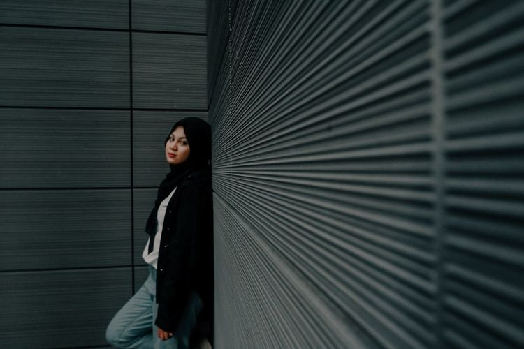 Portrait of a young woman standing against wall