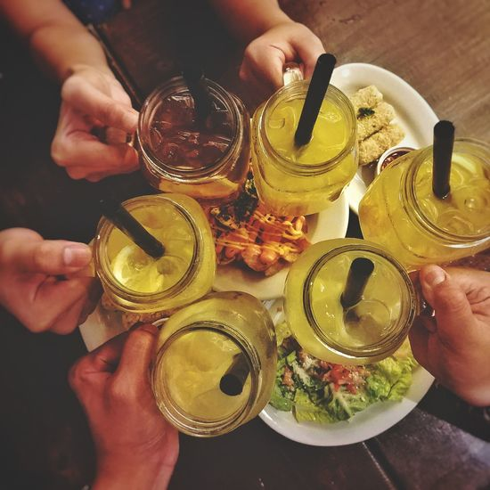 High angle view of people holding drink on table