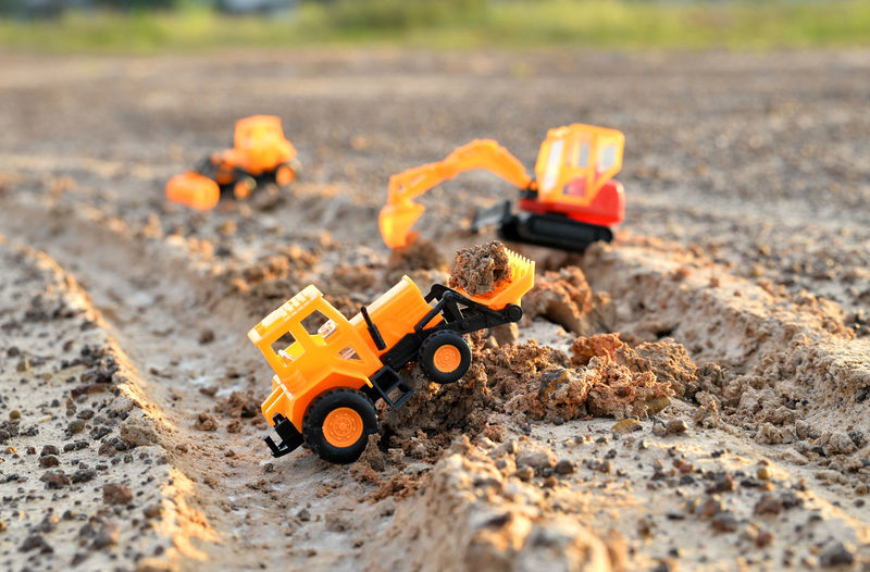 Close-up of toy construction vehicles on dirt