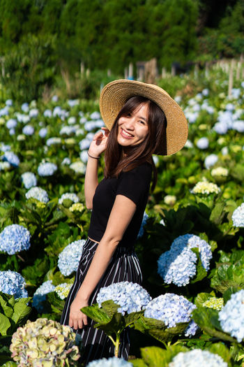 Portrait of smiling woman wearing hat standing amidst flowering plants on field