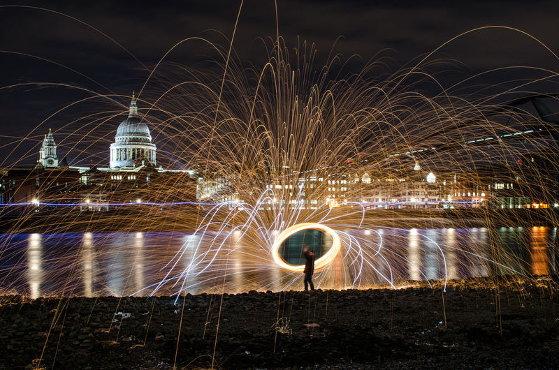 Man with wire wool standing at riverbank against st pauls cathedral