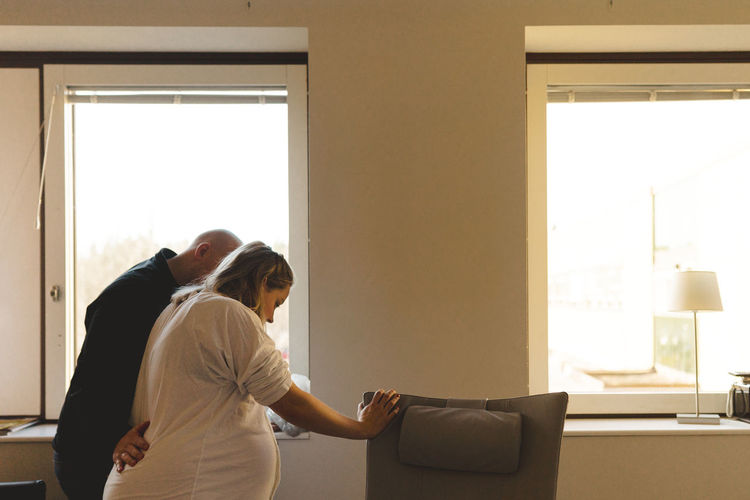 Side view of couple standing against window at home