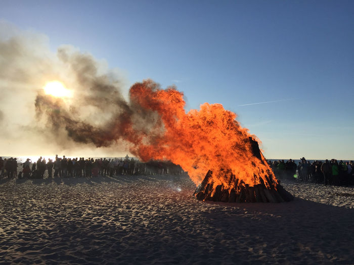 Group of people around fire at beach against sky