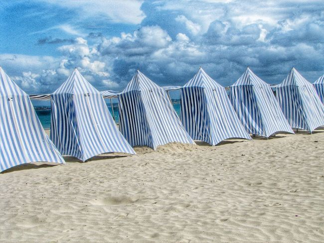 A row of stripy beach tents on a white sandy beach Beach Tents Beach Tent Sand Sandy Sandy Beach White Striped Blue And White