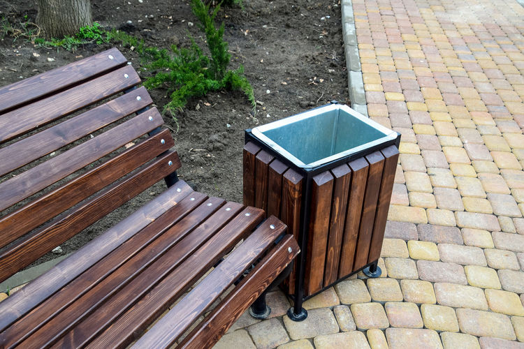 High angle view of wooden bench by garbage can on footpath at park