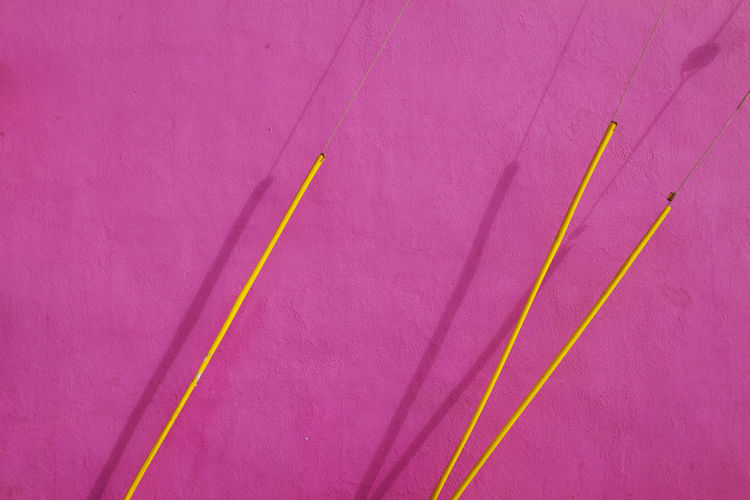 Yellow wires against pink wall during sunny day