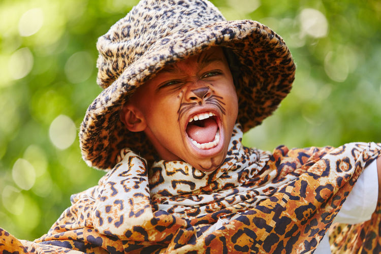 Close-Up Of Boy Imitating Leopard In Yard