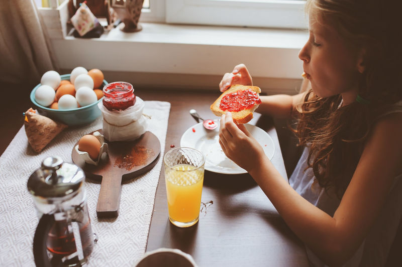 happy kid girl having breakfast at home, eating toast with jam and eggs on farmhouse kitchen Table Food And Drink Indoors  One Person Lifestyles Real People Food Breakfast Kids Childhood Eating Toast Orange Juice  Countryside Farm House Kitchen Morning Eggs Rural Country Life