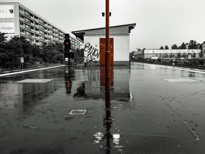 Wet road in city against sky