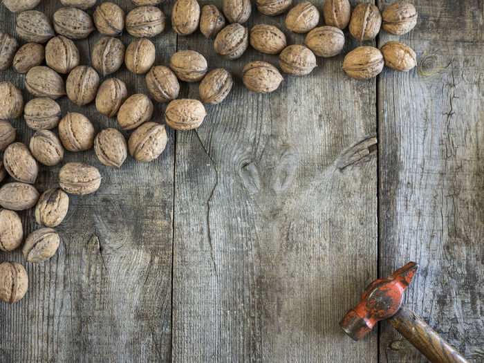 High angle view of walnuts with hammer on table