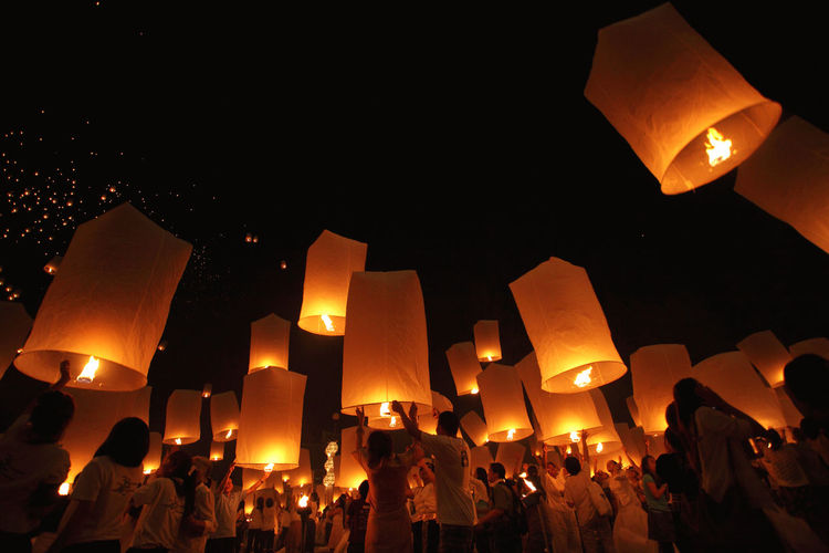 Low angle view of people releasing paper lanterns at night