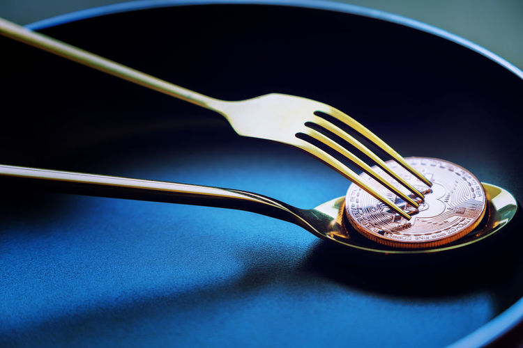 Close-up of bitcoin with fork and spoon in bowl