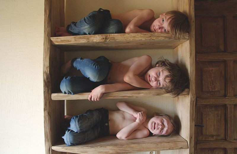 Shirtless boys in wooden shelves at home