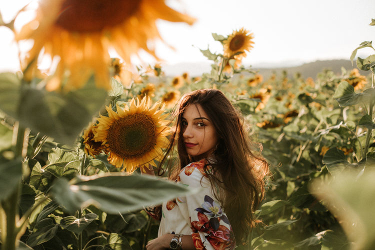 Portrait of woman standing amidst sunflowers