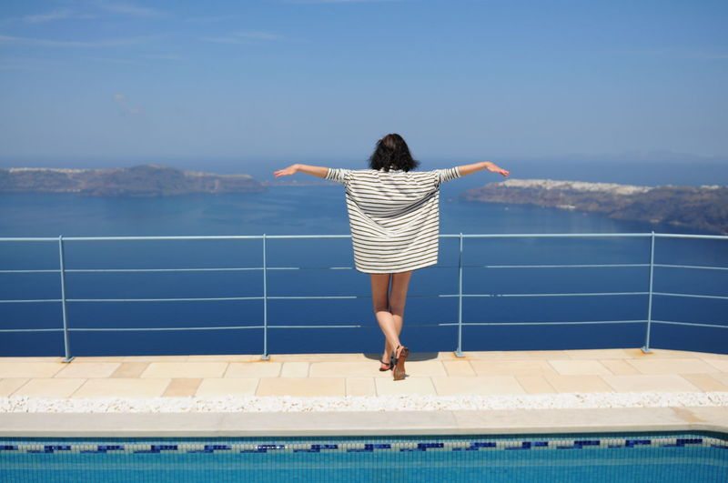 Rear view of woman standing with arms outstretched by railing at poolside against sea