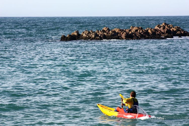 Rear view of man kayaking on sea against clear sky