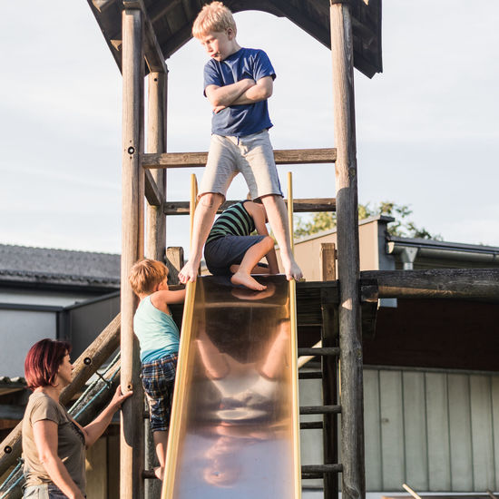 Family Architecture Boys Casual Clothing Childhood Day Elementary Age Friendship Full Length Girls Happiness Leisure Activity Lifestyles Outdoors Playground Playing Real People Sky Slide - Play Equipment Smiling Standing Togetherness This Is Family
