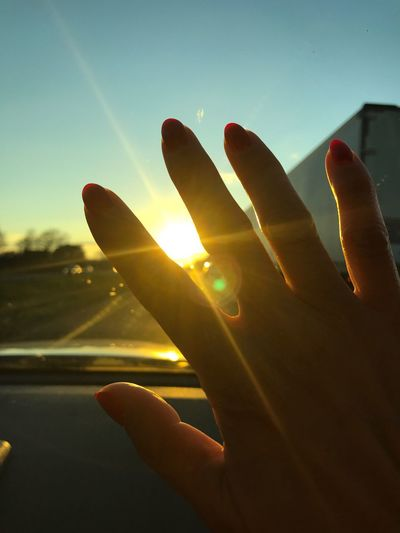 Close-up of hands against sky during sunset