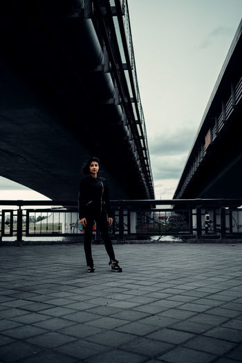 Side view of young woman on bridge against sky in city