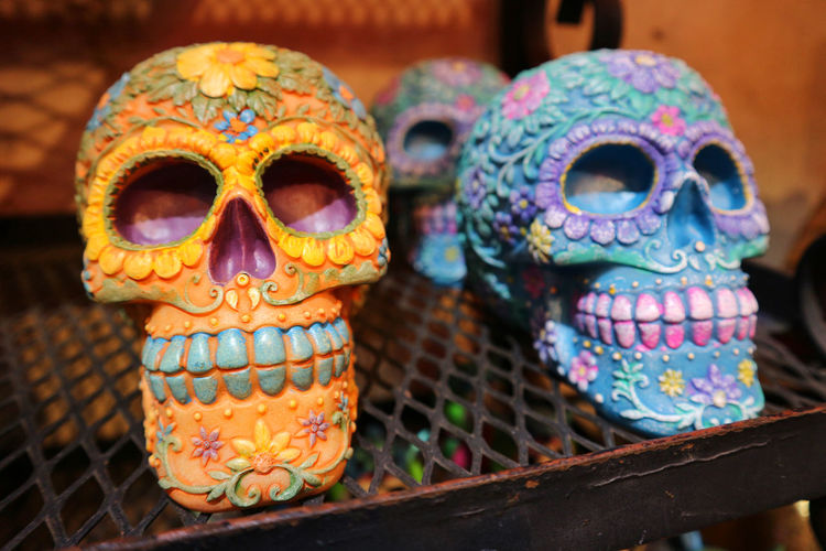 Close-up of colorful human skulls on table