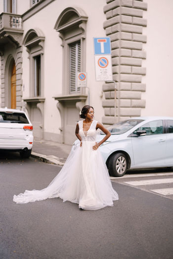 Full length of bride standing on road against building