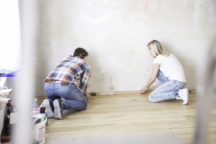 Full length of couple doing carpentry work at home