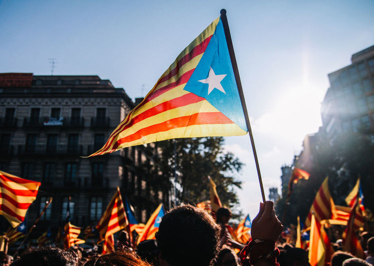 A protestor waves the Catalan flag during celebrations in Barcelona Barcelona Catalan Catalonia Catalunya Celebration Community Democracy Event Government Protest Protests Proud SPAIN Senyera Crowd Day Flag Flags Outdoors Patriotism People Pride Protestor Real People Sky The Week On EyeEm Fresh On Market 2017