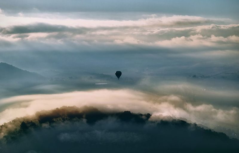 Hot air balloon flying over land against sky